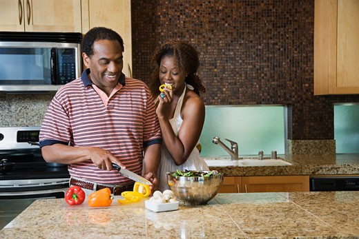 African couple fixing healthy meal in modern kitchen : Stock Photo