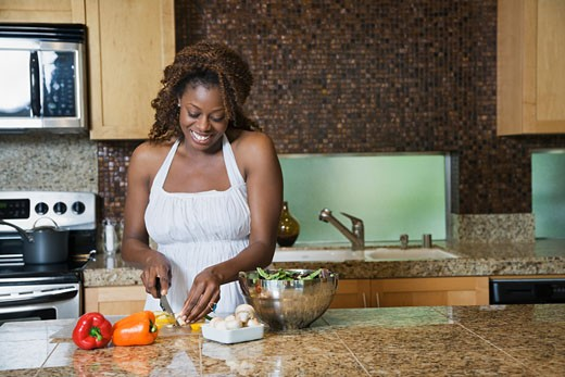 African woman fixing healthy meal in modern kitchen : Stock Photo