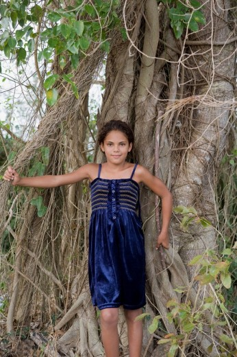 Hispanic girl leaning against mass of tree roots : Stock Photo