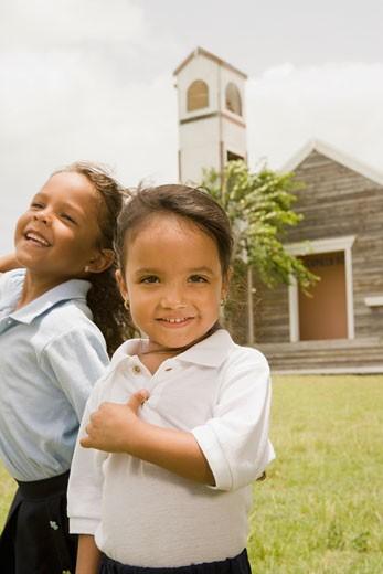 Hispanic sisters standing outside church : Stock Photo
