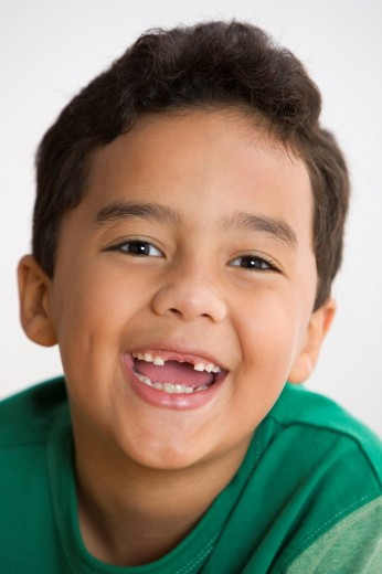 Toothless mixed race boy smiling : Stock Photo