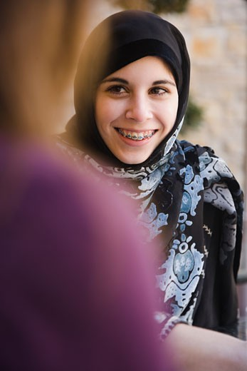 Middle Eastern teenager in headscarf talking to mother : Stock Photo