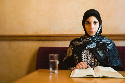Middle Eastern teenager in headscarf reading book : Stock Photo