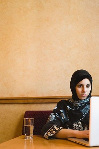Middle Eastern teenager in headscarf using laptop : Stock Photo
