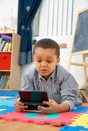 Mixed race boy playing video game : Stock Photo