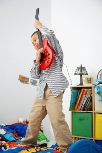 Mixed race boy playing toy guitar : Stock Photo