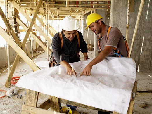 Hispanic workers looking at blueprints on construction site : Stock Photo