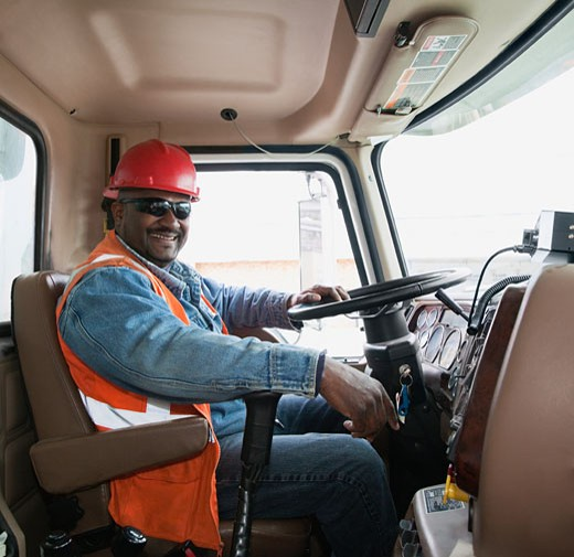 African construction worker driving truck : Stock Photo