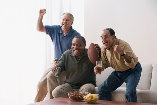 Men watching football game in living room with snacks : Stock Photo