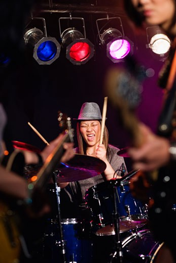 Asian woman playing drums onstage : Stock Photo