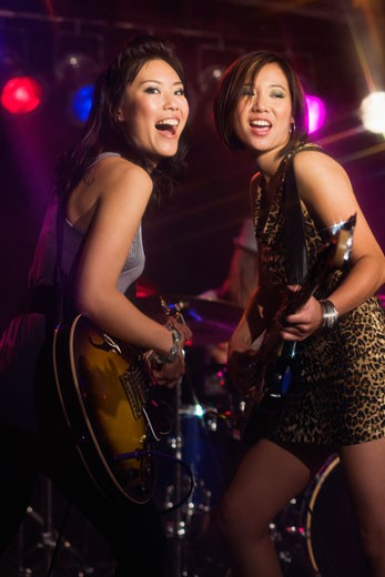Asian women playing electric guitar onstage : Stock Photo