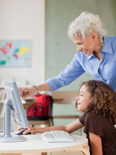 Teacher and student using computer : Stock Photo