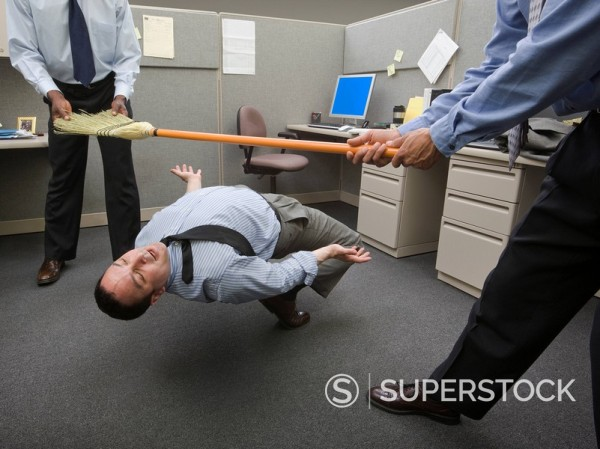 Stock Photo: 1589-78397 Businessmen playing limbo with broom in office