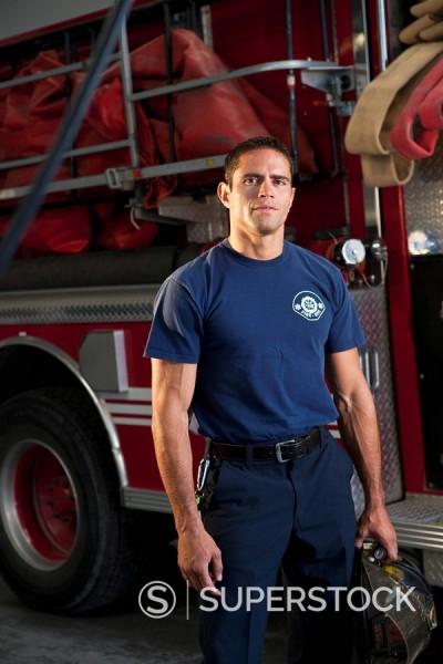 Stock Photo: 1589-78398 Hispanic fireman standing by fire engine