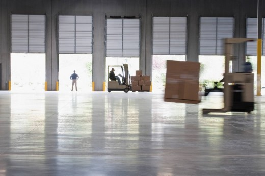 Forklifts moving pallets in warehouse : Stock Photo