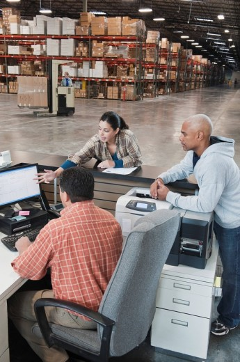 Workers using computer in warehouse : Stock Photo