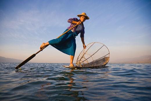 Burmese woman using legs to row on lake : Stock Photo