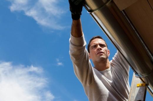 Hispanic man installing gutter on house : Stock Photo