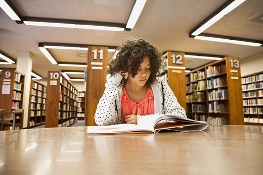 Mixed race girl studying in library : Stock Photo