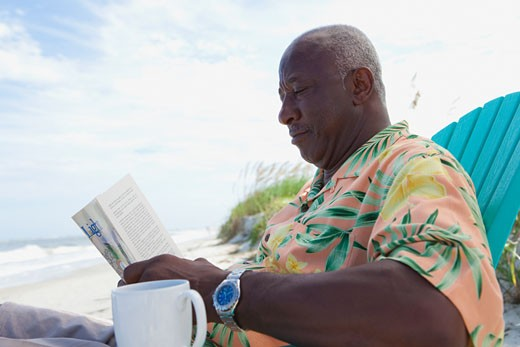 Senior African man reading newspaper at beach : Stock Photo
