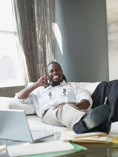 African businessman with feet up talking on cell phone : Stock Photo