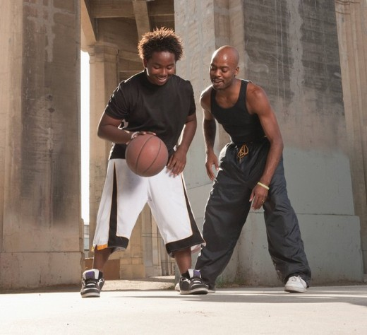 African father playing basketball with son : Stock Photo