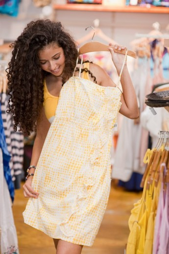 Israeli teenage girl looking at dress in store : Stock Photo