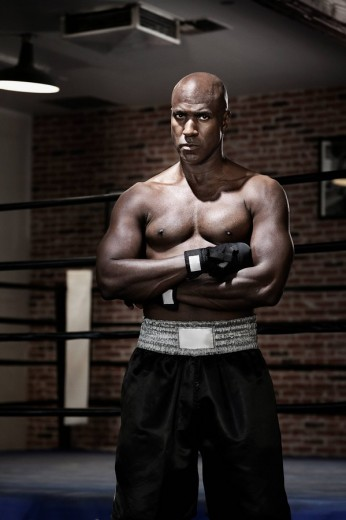 Intense African boxer with arms crossed : Stock Photo