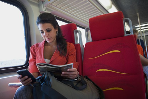 Hispanic woman using cell phone on train : Stock Photo