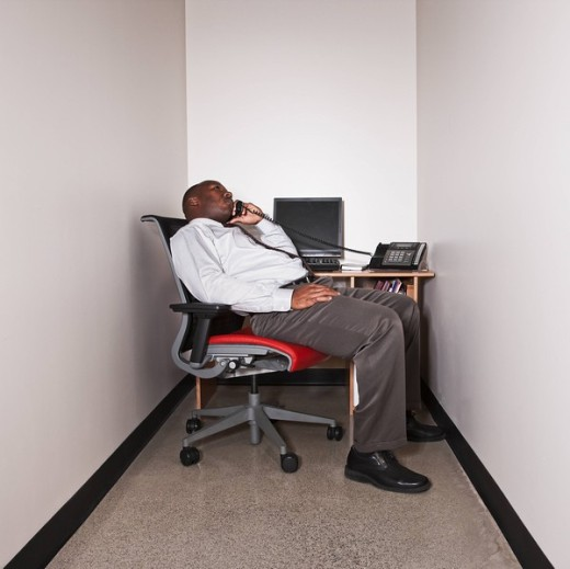 African businessman talking on phone in small office : Stock Photo