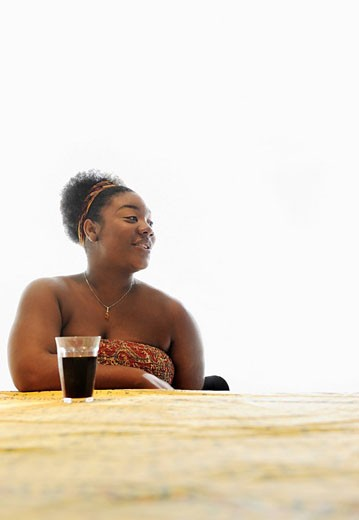 African American woman drinking soda at table : Stock Photo