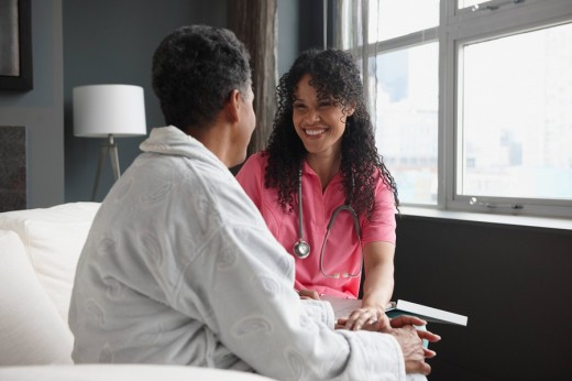 African American nurse checking on patient : Stock Photo