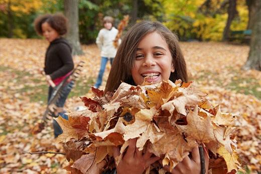 Children raking autumn leaves : Stock Photo