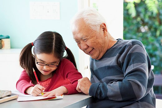 Japanese grandfather helping granddaughter with homework : Stock Photo