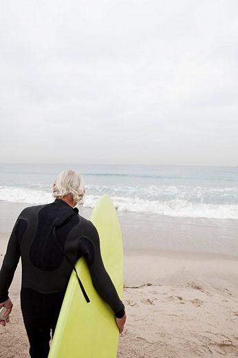 Senior Hispanic man carrying surfboard : Stock Photo