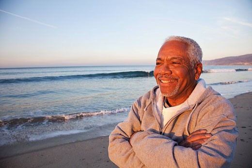 African American man standing on beach : Stock Photo