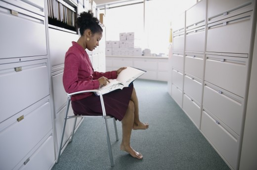 Stock Photo: 1589R-01076 Side profile of a businesswoman sitting on a chair reading a file