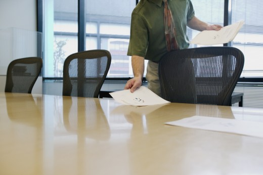 Stock Photo: 1589R-01117 Businessman holding sheets of paper standing at a table