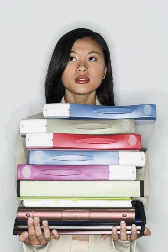 Teenage girl standing holding a stack of files : Stock Photo