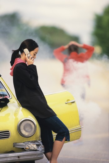 Stock Photo: 1589R-01818 Young woman leaning against a car talking on a mobile phone