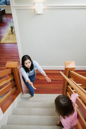 Mother reaches for child at top of stairs : Stock Photo