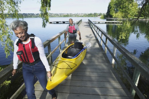 Stock Photo: 1589R-0191 Elderly couple carrying a kayak walking on a pier