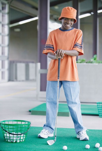 Stock Photo: 1589R-0210 Young boy standing next to a basket of golf balls holding a golf club at a golf course