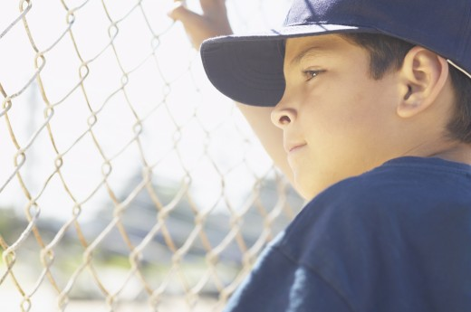Young boy standing holding a chain link fence : Stock Photo