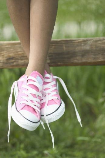 Legs of a child dangling from a fence : Stock Photo