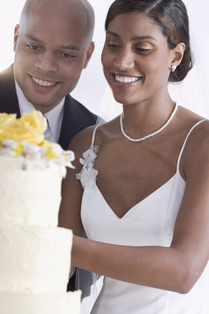 Bride and groom looking at their wedding cake : Stock Photo