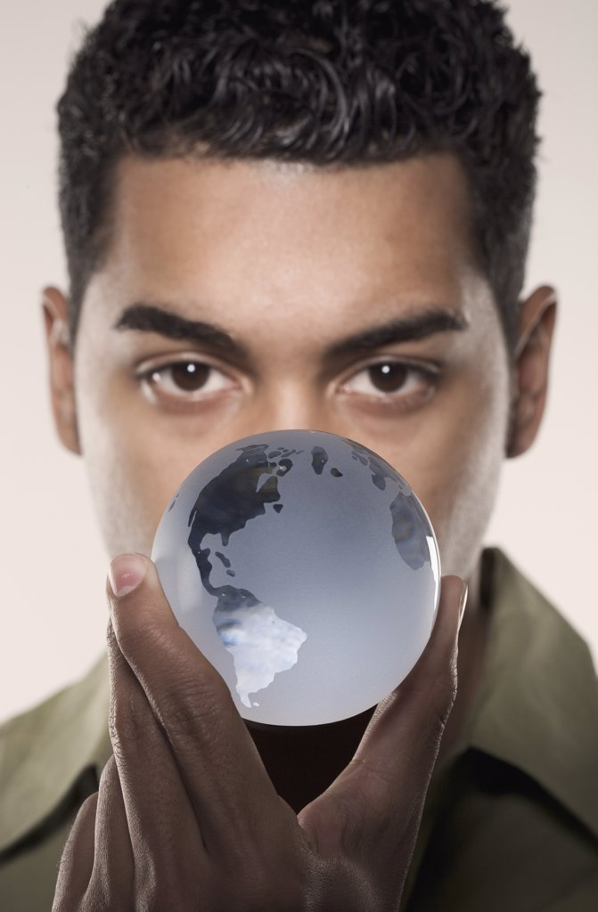 Stock Photo: 1589R-02648 Young man holding a glass globe
