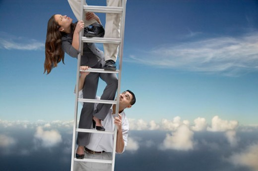Stock Photo: 1589R-02890 Two young businessmen and a young businesswoman climbing a ladder