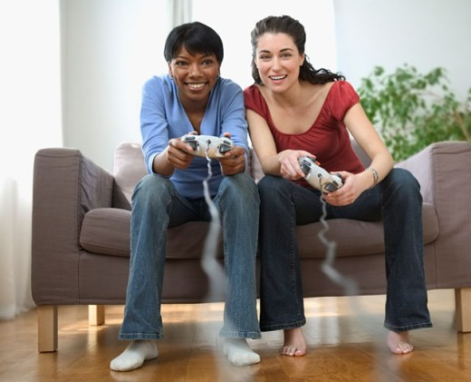 Two young women playing video games : Stock Photo