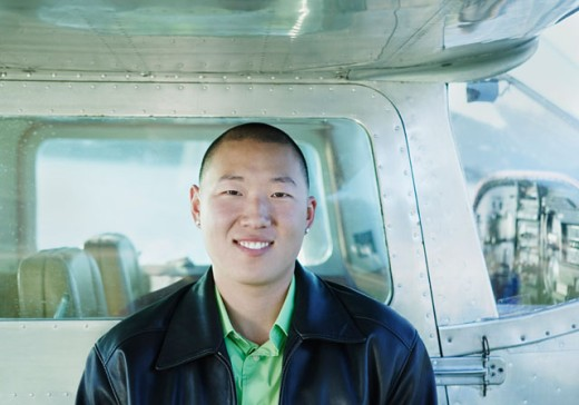 Stock Photo: 1589R-0325 Portrait of a young man smiling leaning against the side of a plane